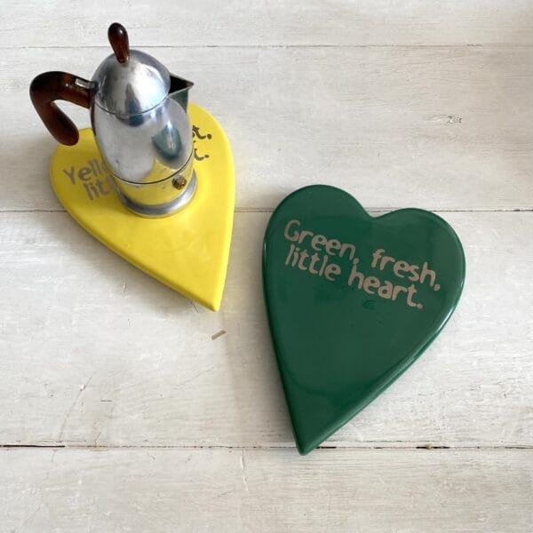 una moka è appoggiata su un sottopentola a forma di cuore giallo accanto ad uno uguale solo di colore verde